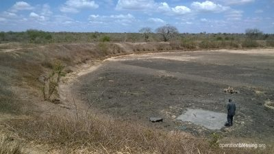A man stands in the remnants of a body of water, dried by drought.