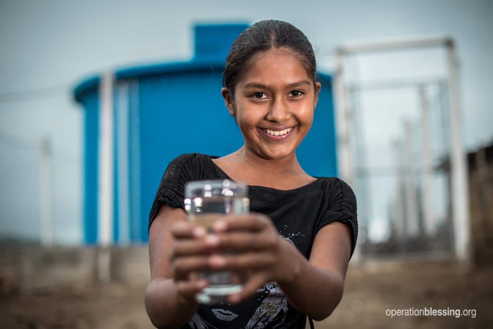 A young girl holds a glass of water safe for drinking!