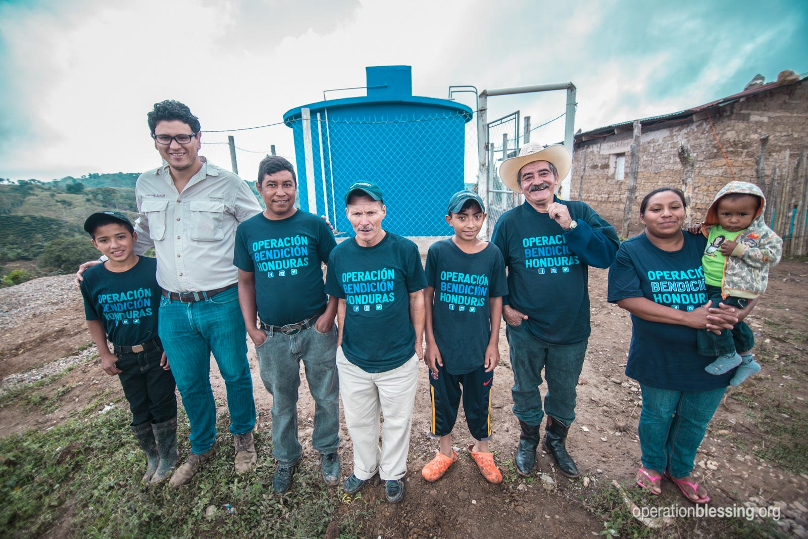 Residents of El Campanario stand near their new 5,000-gallon water tank.