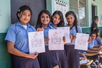 Four girls proudly display their diplomas at the end of the school year.