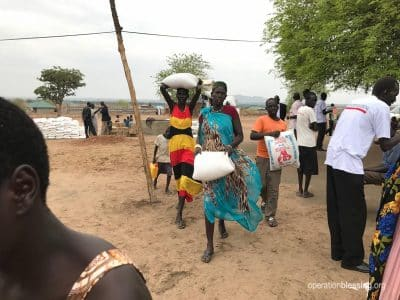 Famine stricken families in South Sudan walk home with donated food.