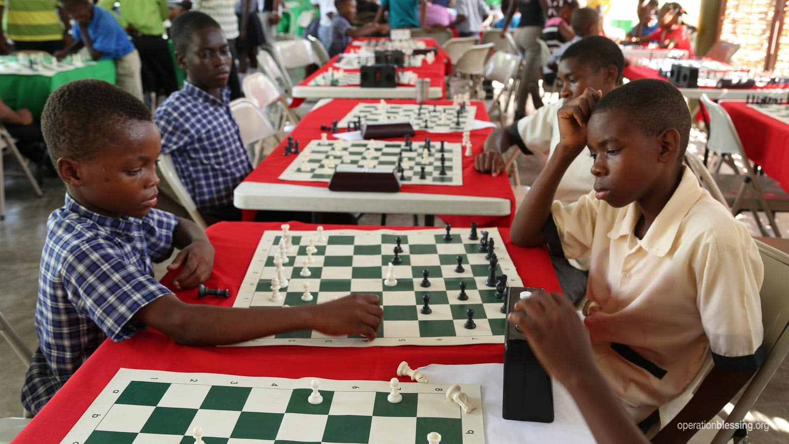 Children learn critical thinking and problem solving skills at chess competition at Operation Blessing's ENLA school in Haiti.