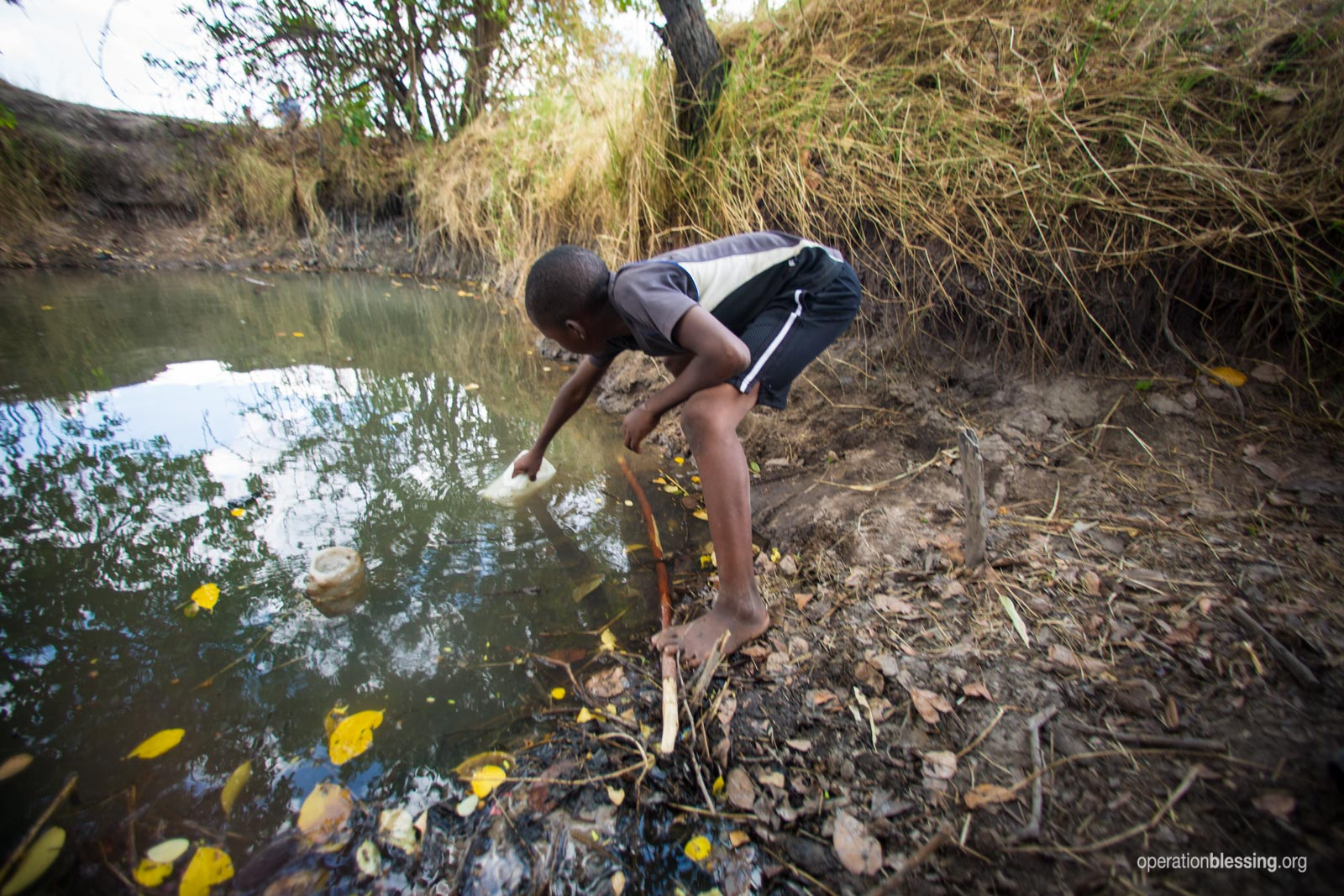 A child retrieves dirty water.