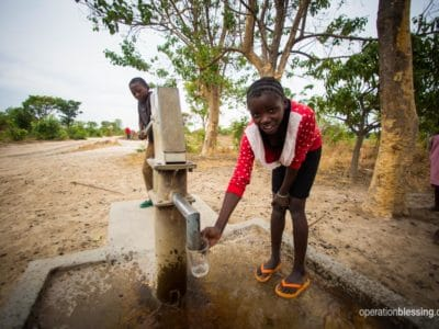 Water spurts out of the new water source in Nsansa.