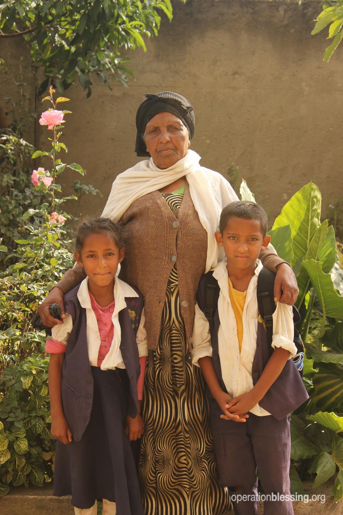 Hibre stands with her grandchildren.