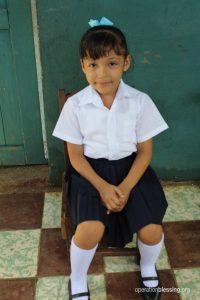 Aylin sits in her school uniform.
