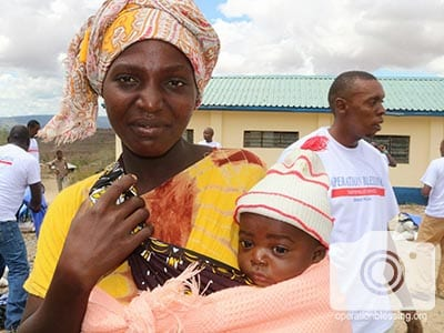 A mother smiles, thankful for food to help feed hungry Kenyans like herself and her baby.