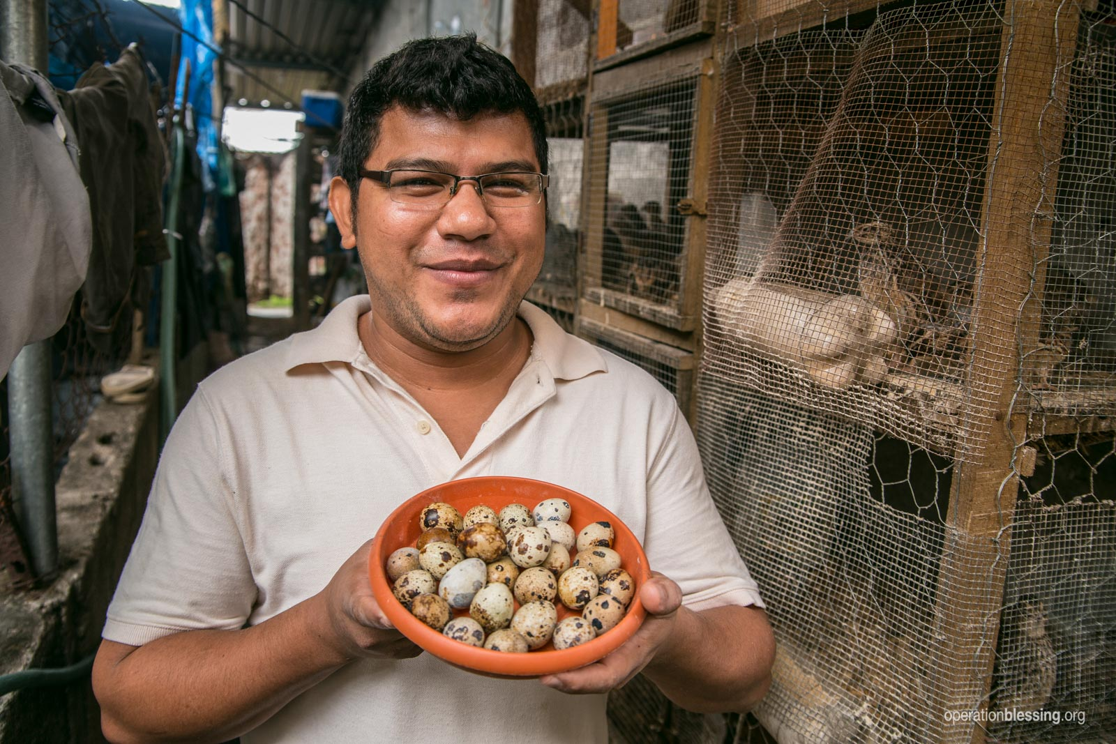 Julian poses with quail eggs form his successful business.