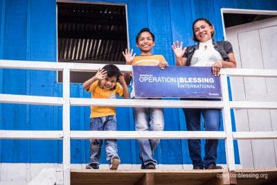 Sergio and his family wave from their new house.