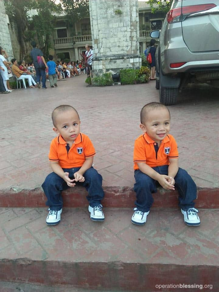 Twins Luis and Lorenzo, seated on a step, now have straight, corrected feet thanks to MiracleFeet and Operation Blessing.