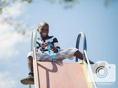 A Haitian boy smiles atop a slide, grateful for learning and playing on the field trip.