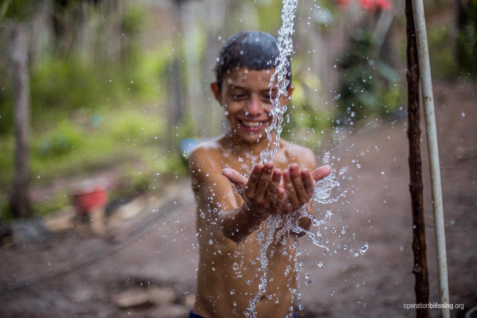 A boy soaks in the simple pleasure of abundant safe water.