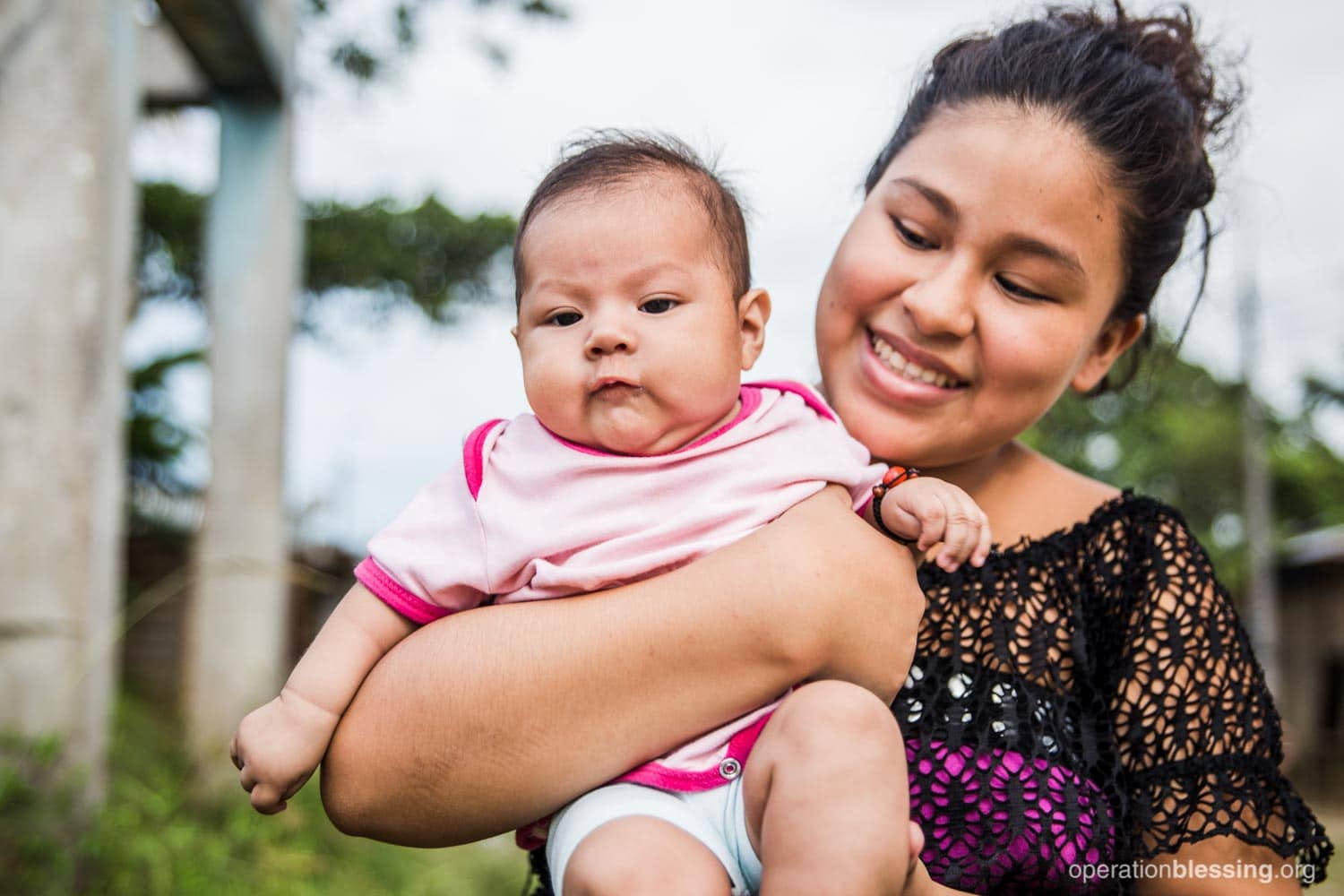 Asslin holding her healthy baby girl after both survived preeclampsia thanks to prenatal classes in Peru.