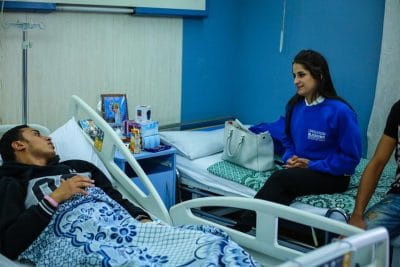 An Operation Blessing team member sits in the hospital room of an attack victim.