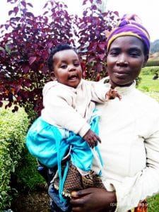 Bayavuge smiles holding her child, thankful they are both eating healthy now.