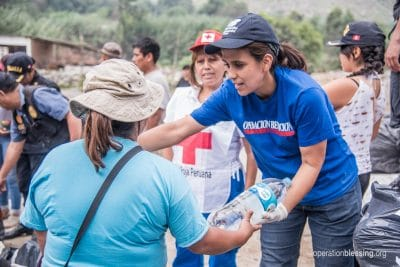 Sandra hands out water to flooding and mudslide victims.