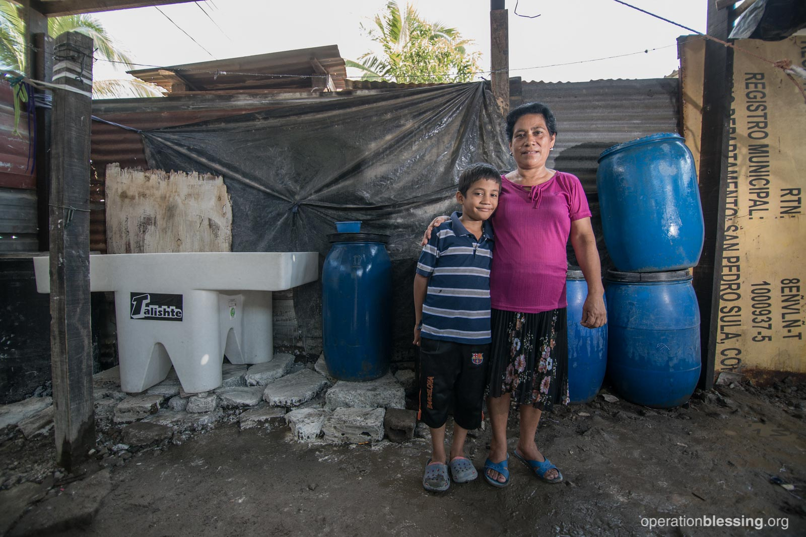 Mercedes and her son pose in front of their new pila and water containers.
