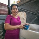 Mercedes stands next to a new pila (wash basin) which will help her to protect her family from Zika-carrying mosquitoes.