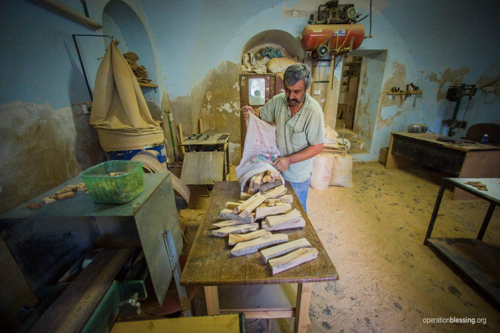 Joseph lays out wood to work in his shop.