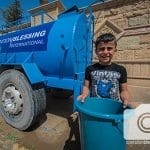 A boy holds a bucket of water in his city recently liberated from ISIS.