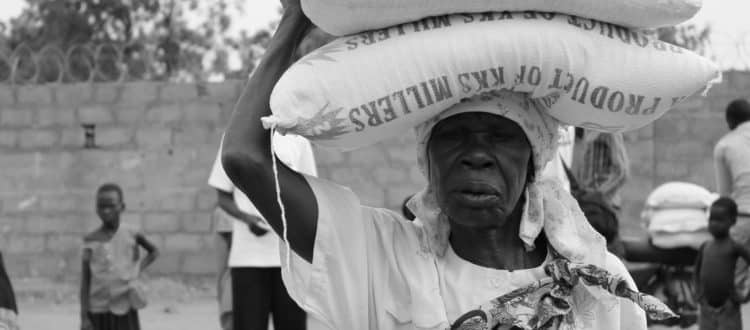 An elderly woman carrying relief on her head.