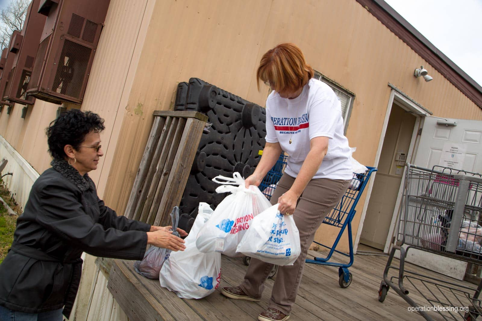 Amarilis receives groceries from a volunteer.