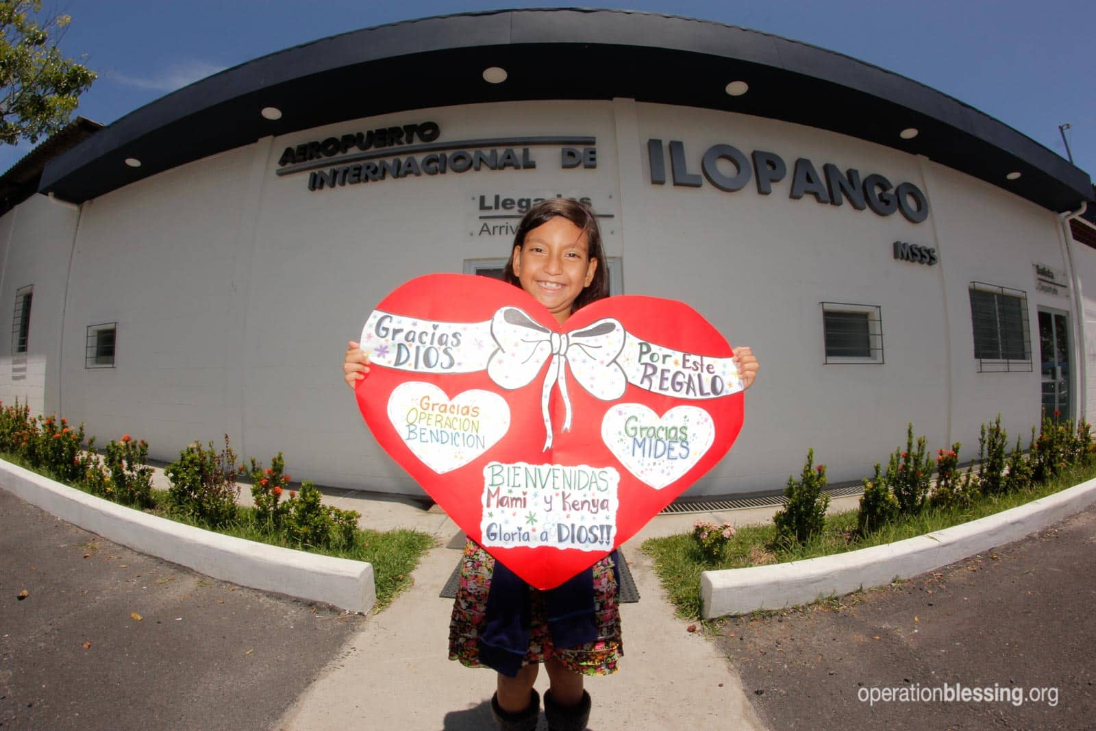 Kenya holds up a thank you sign shaped like a heart after her heart surgery.