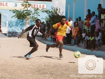 Two players chase down a soccer ball at the chess and soccer tournament at our ENLA School in Haiti.