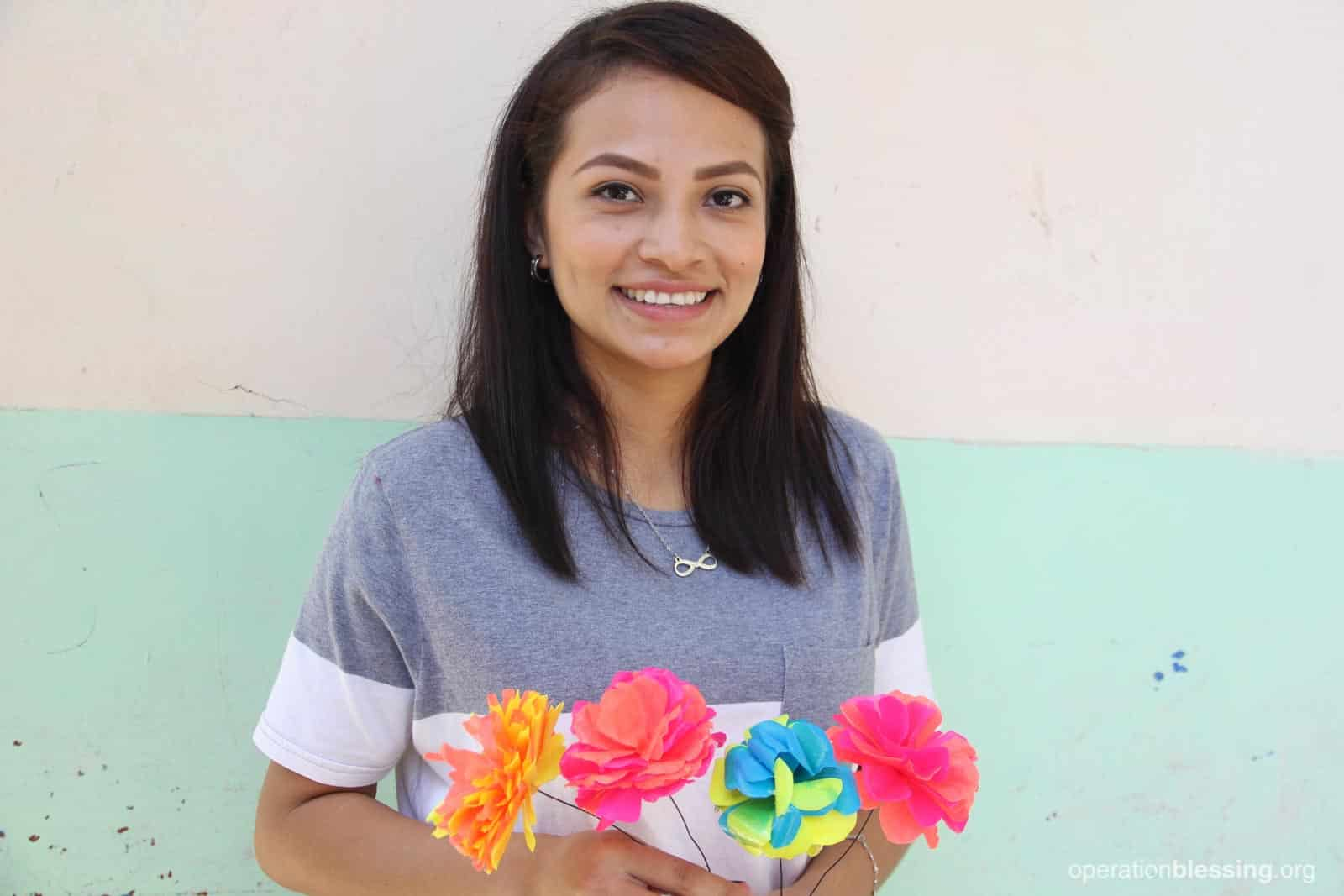 Maria holds colorful paper flowers she learned to make. This opportunity has given her a new life.