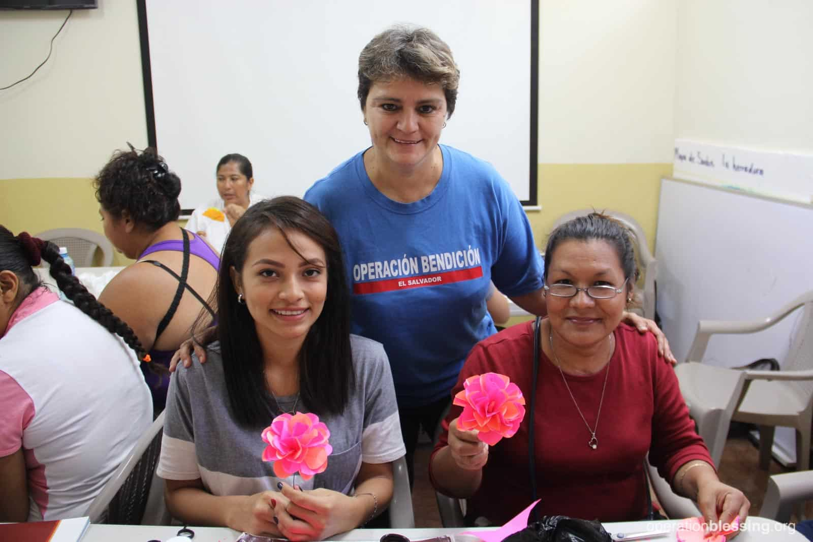 Maria and her mother sit side by side holding their paper flowers as an Operation Blessing worker shows her support.