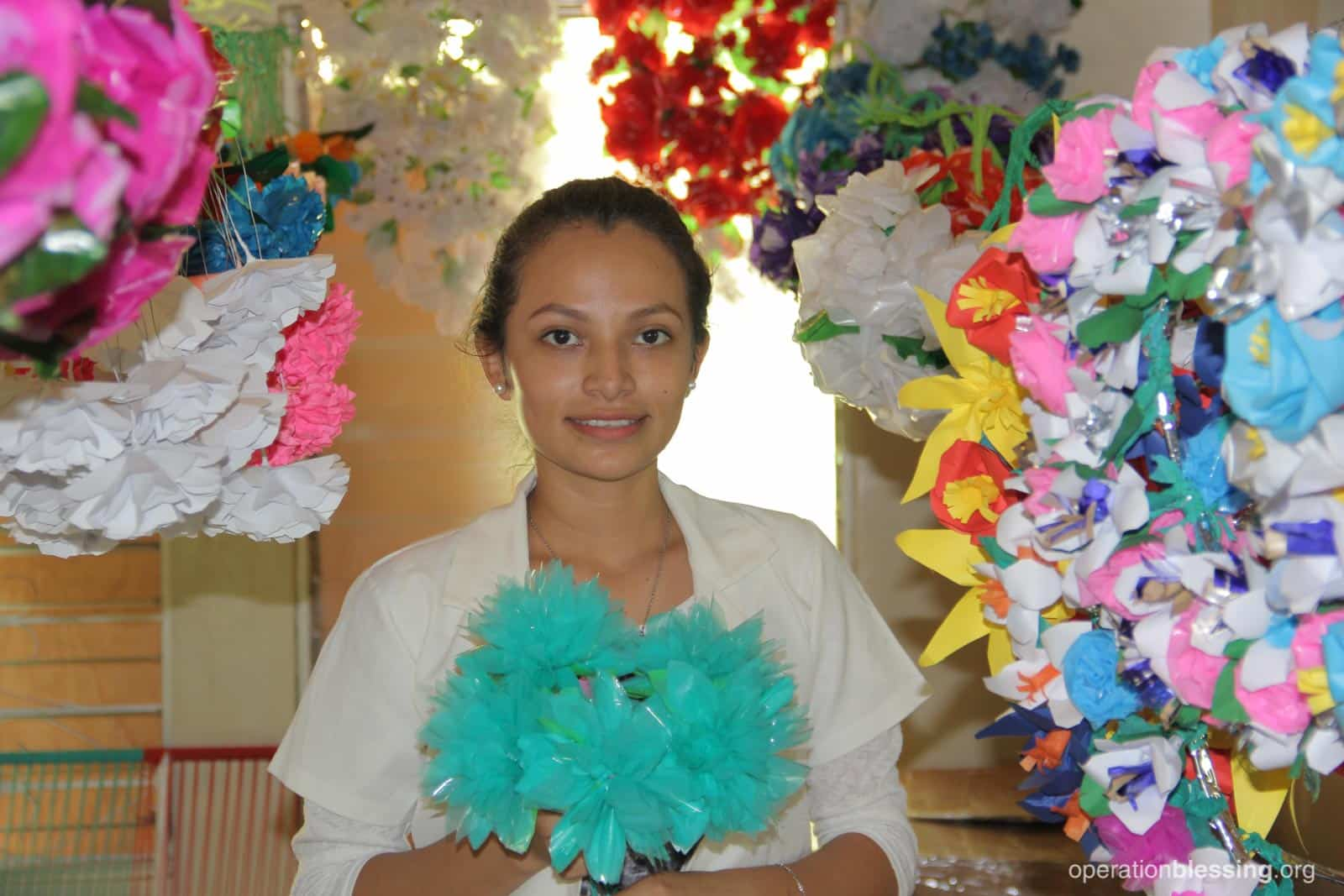 Maria stands surrounded by beautiful paper flowers, which she now sells as a successful business.