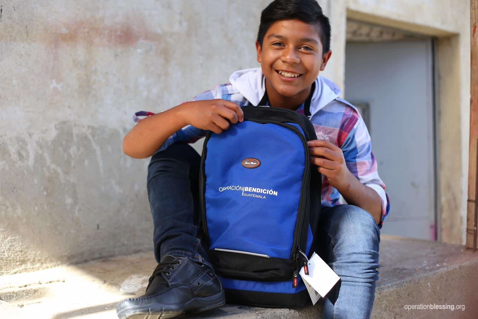 Edinson shows off the new school supplies and brand new shoes he received from OBI.