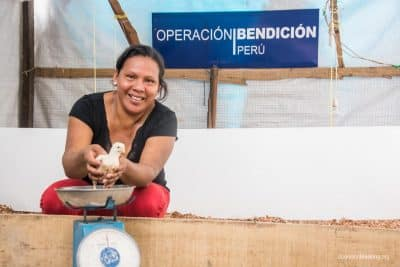 Mery, a mother of two, weighs one of the baby broiler chicks she received from Operation Blessing to help her begin her poultry breeding business.