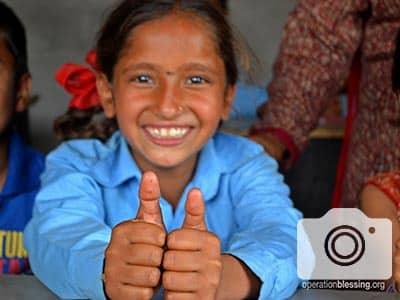 A girl gives thumbs up to the camera. She is only one of the Nepalese earthquake victims helped by this school.