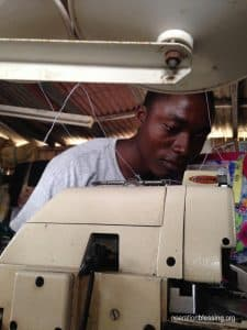 Samuel works at his sewing machine.