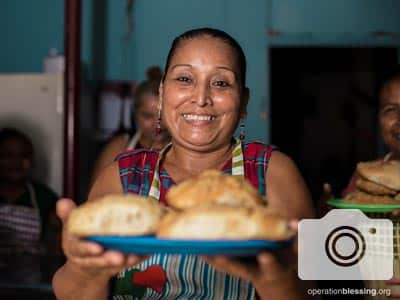 A smiling woman presents baked goods prepared in the Women of Hope bakery in Honduras.