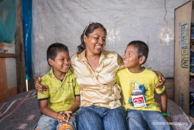 Maria and her kids smile, thankful for her restored cervical health.