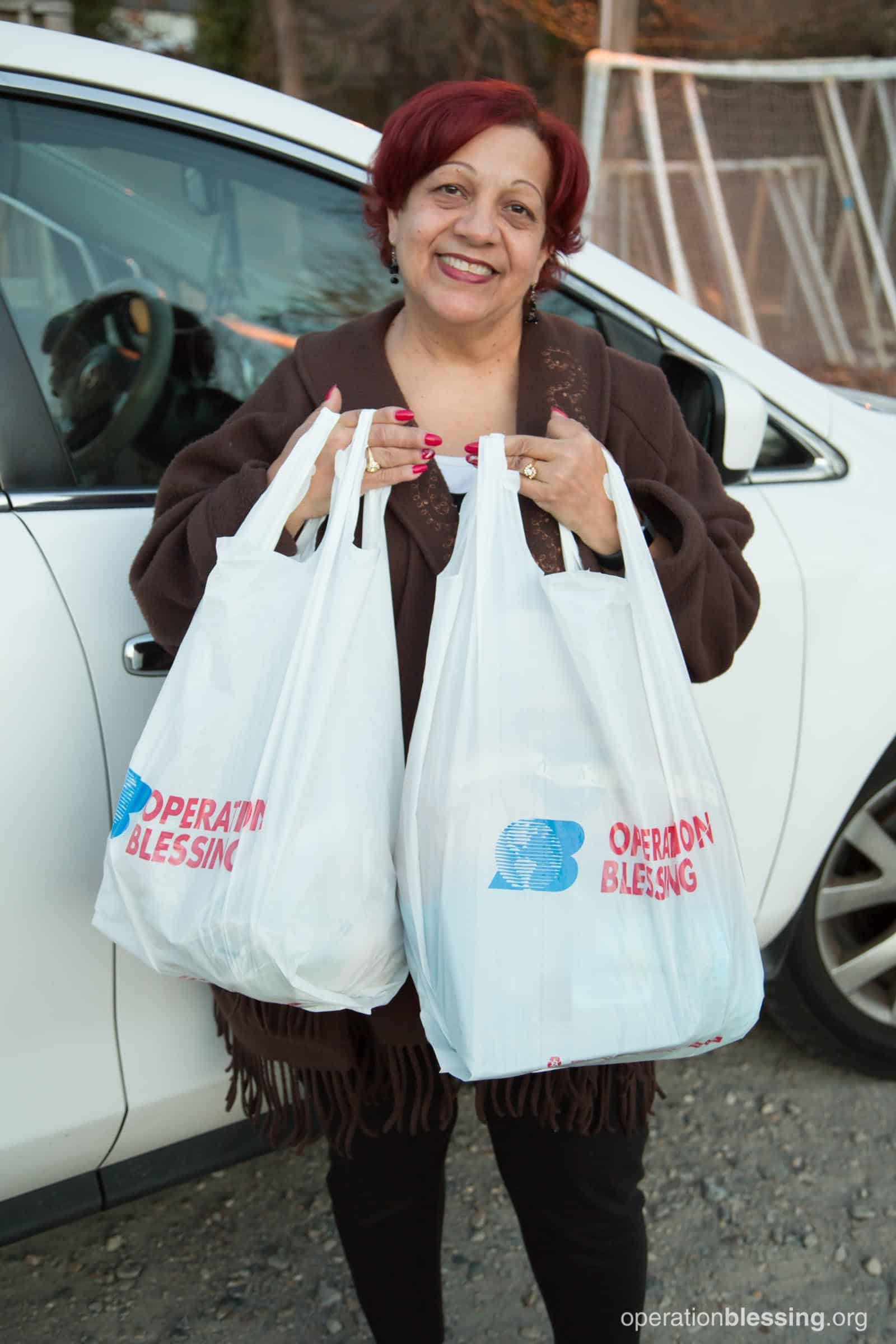 Clara holds free groceries from Operation Blessing partner House of Blessing in Chesapeake.
