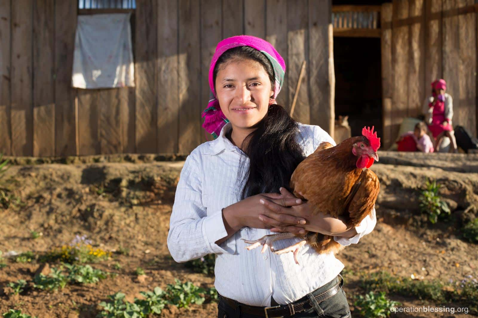 A young woman holds a chicken on a chicken farm in Honduras.