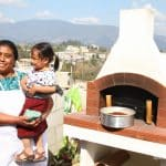Miriam stands with her daughter in front of the oven that kick-started her baking business.
