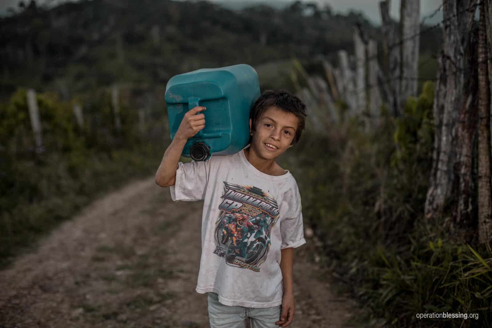 Omar carries a container of water.