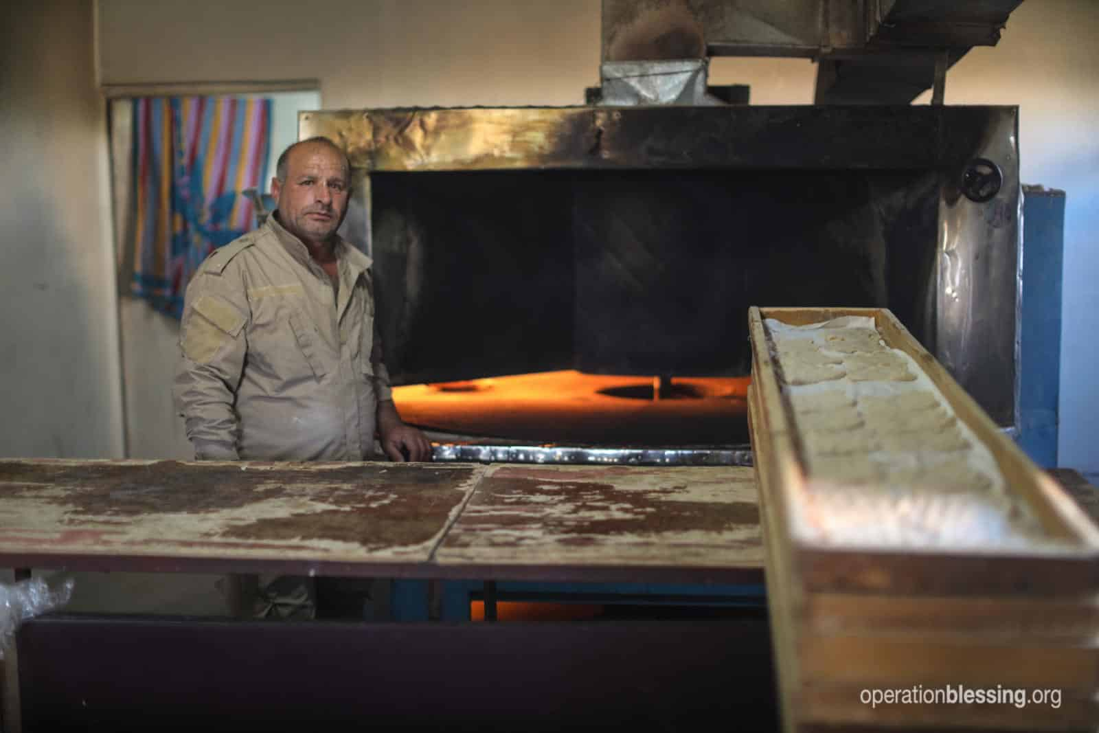 A baker stands at his new oven, bread cooking again for the first time since ISIS was driven out.