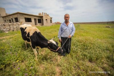 A farmer stands with his cow, donated by Operation Blessing.