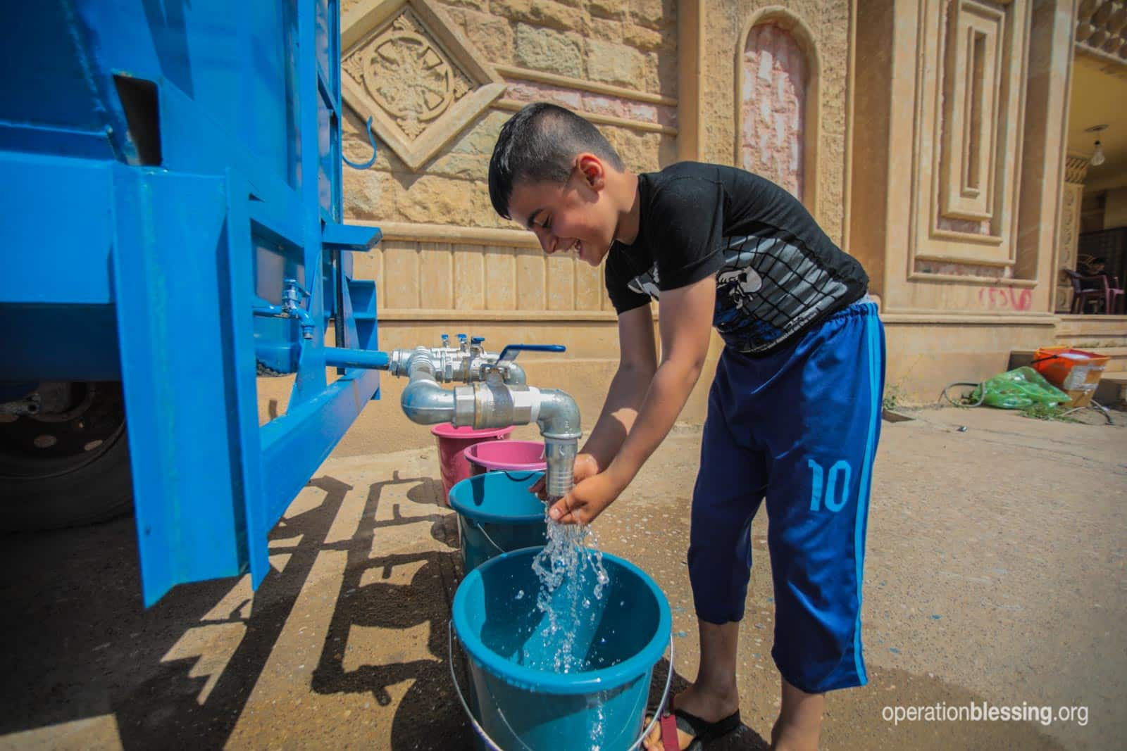 A boy collects water from the Operation Blessing-provided tap.