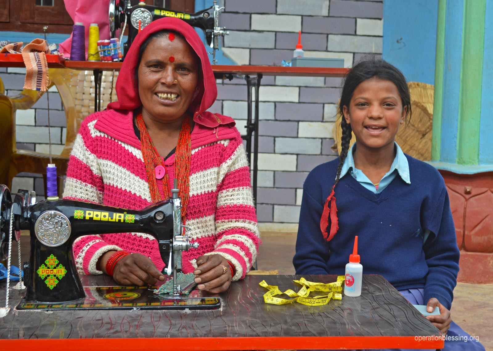Sushila sits at her sewing machine next to her daughter.