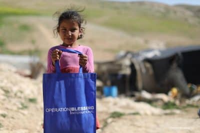 A Bedouin child holds a bag filled with relief.