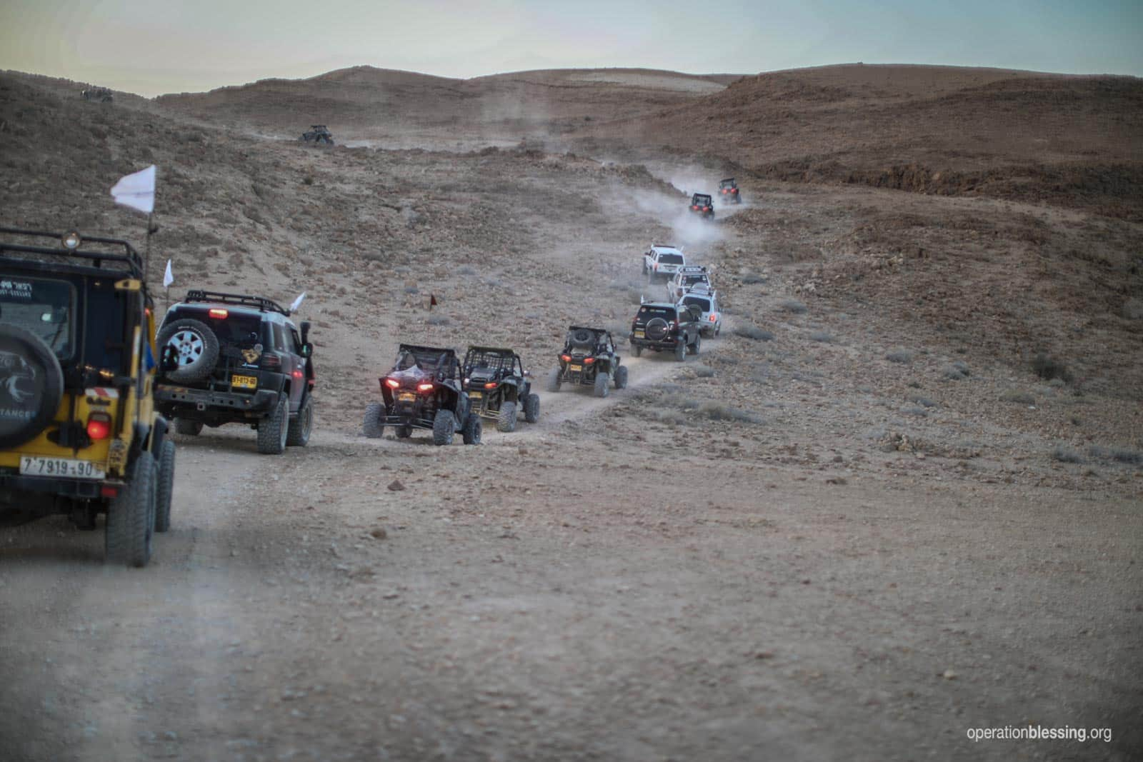 The convoy travels the desert with relief.