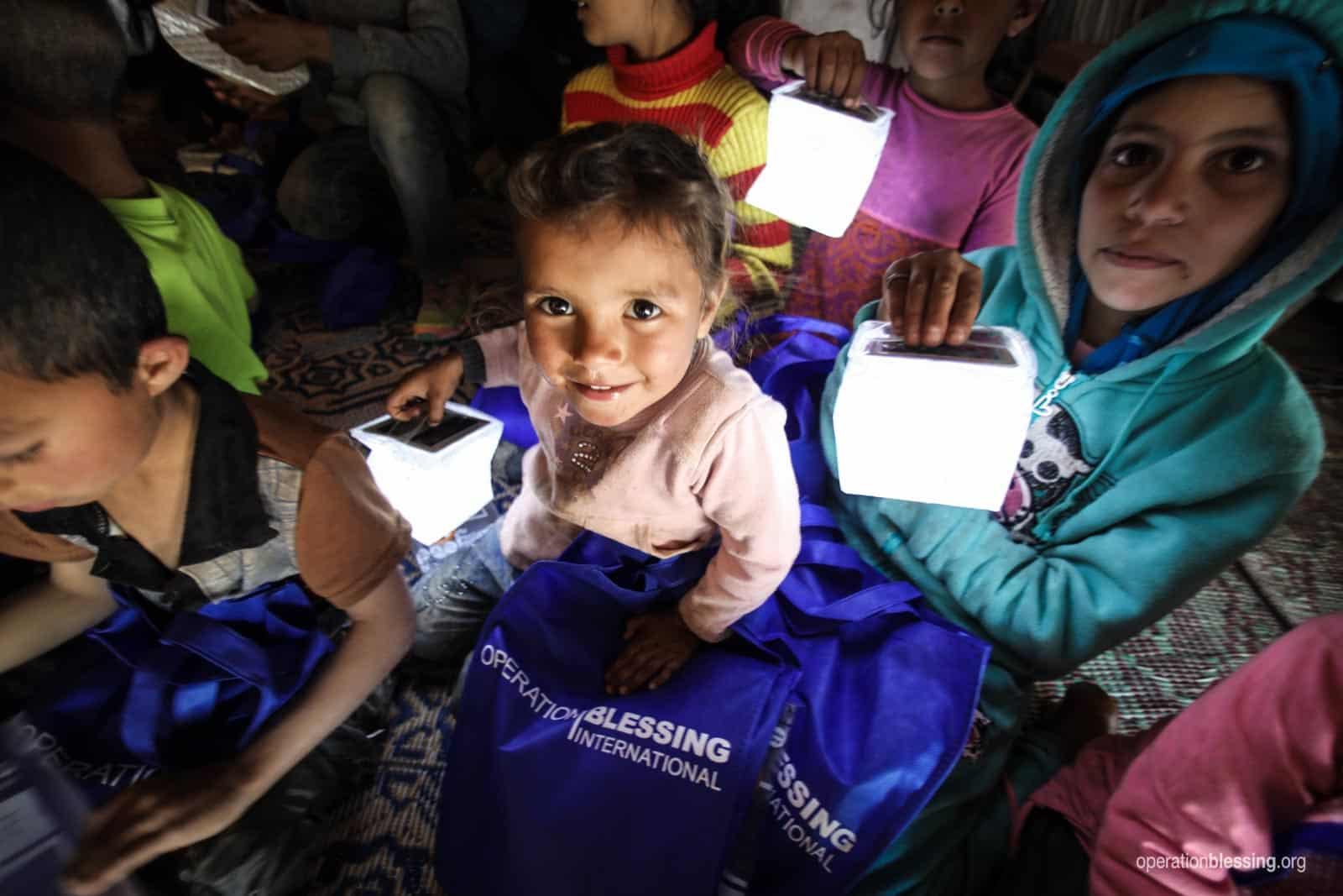 Children smile as they hold solar lanterns.