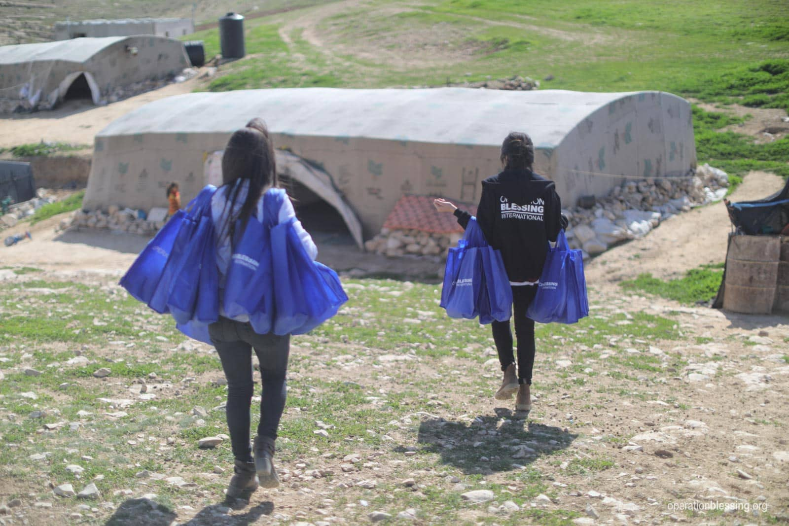 Volunteers carry bags filled with relief for Bedouin families.