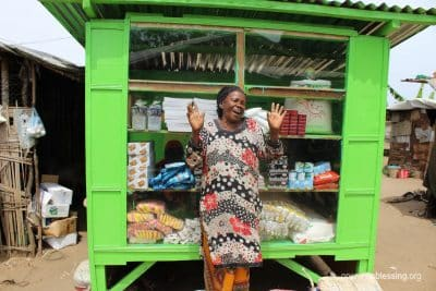 Ma Kemah stands in front of her store, thankful for the business opportunity.